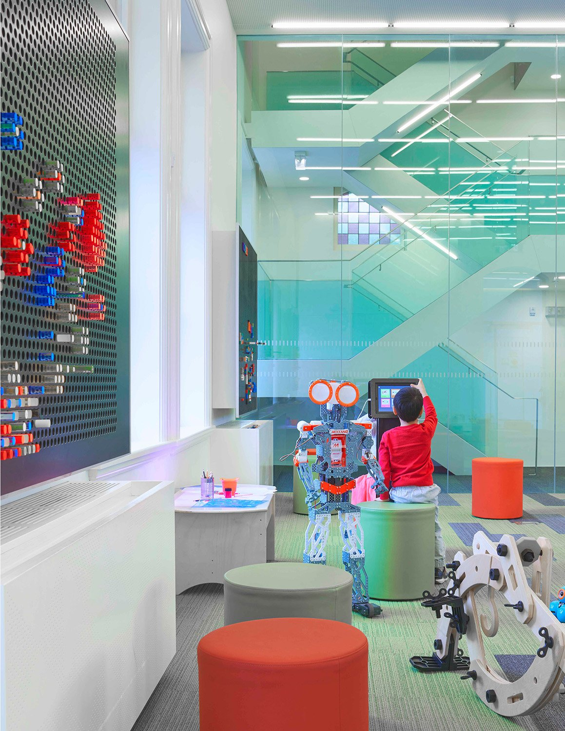 The children's Discovery Centre is equipped with smart tables, touch-screen tablets and robot building kits. A glazed staircase leads to the Makerspace studio above. Tom Arban