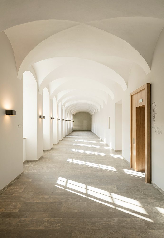 The reception becomes a mediating center between the old and new building – dominated by light natural stone and leather. HGEsch, Hennef