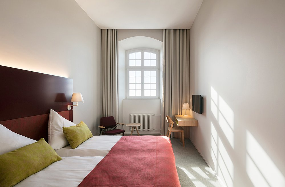 The colours in the hotel rooms are reduced to three: midnight blue, ox blood red and mustard yellow. They are used in different combinations as accents in every room. HGEsch, Hennef