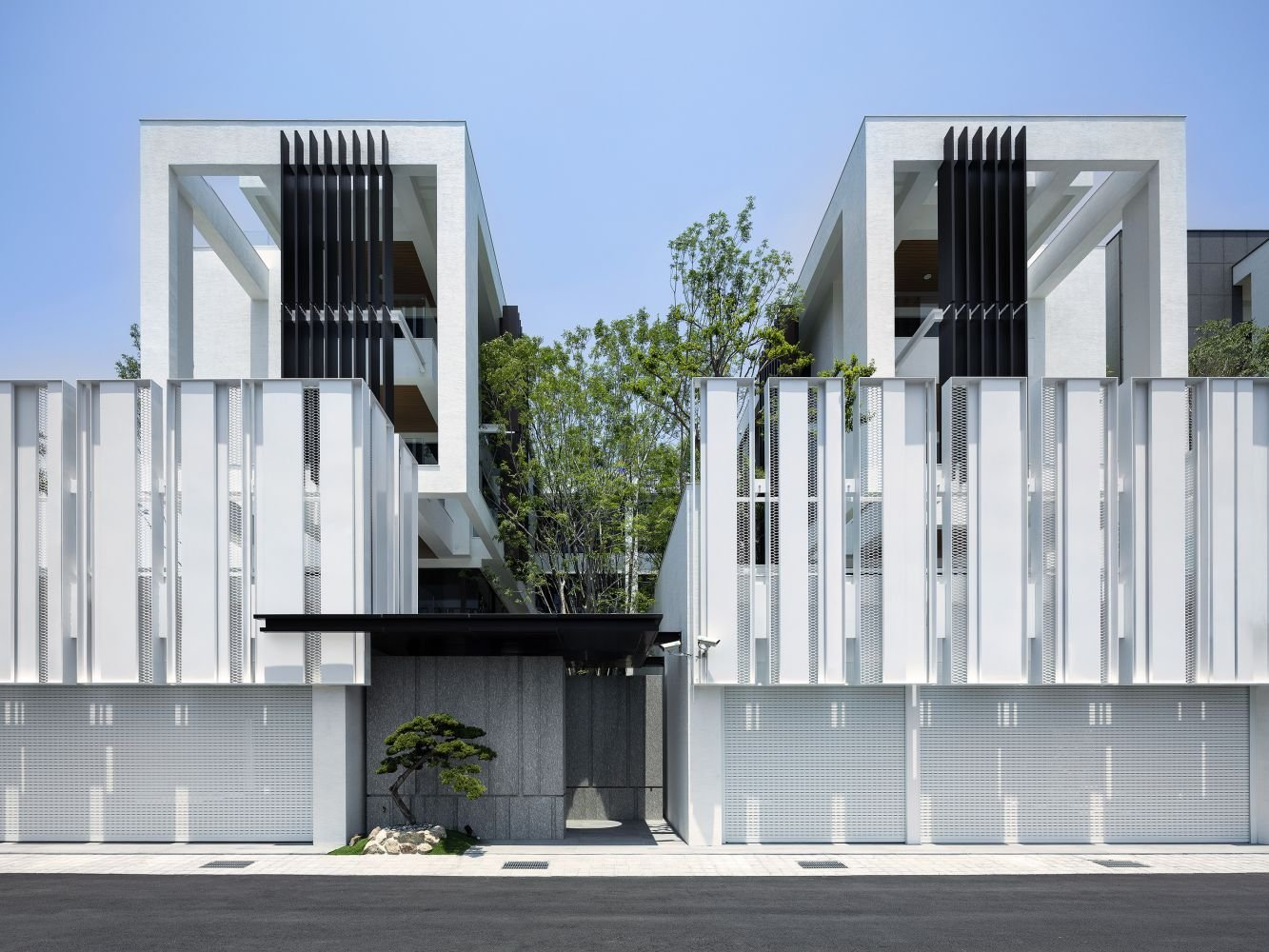 Multiple vertical metallic pillars blend in with the green environment. Moooten Studio/ Qimin Wu