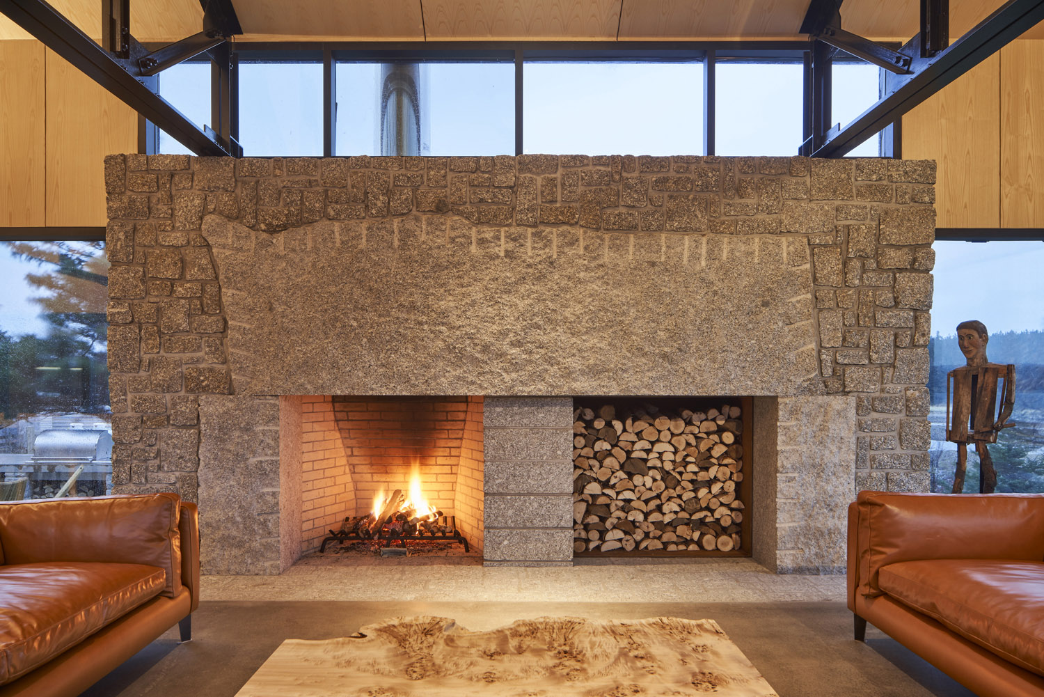 The 16' granite fireplace. The five-tonne live-edge mantle stone carries the marks of its making. doublespace photography inc
