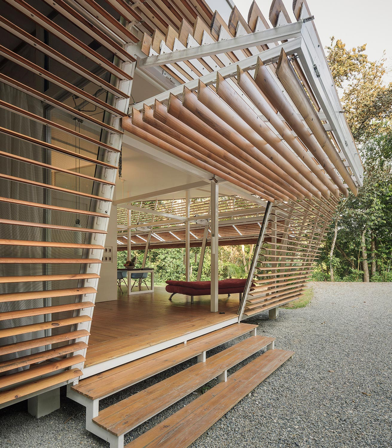 The outer timber-slat walls are set at an incline to reduce the direct impact of sunlight and rainwater. Fernando Alda