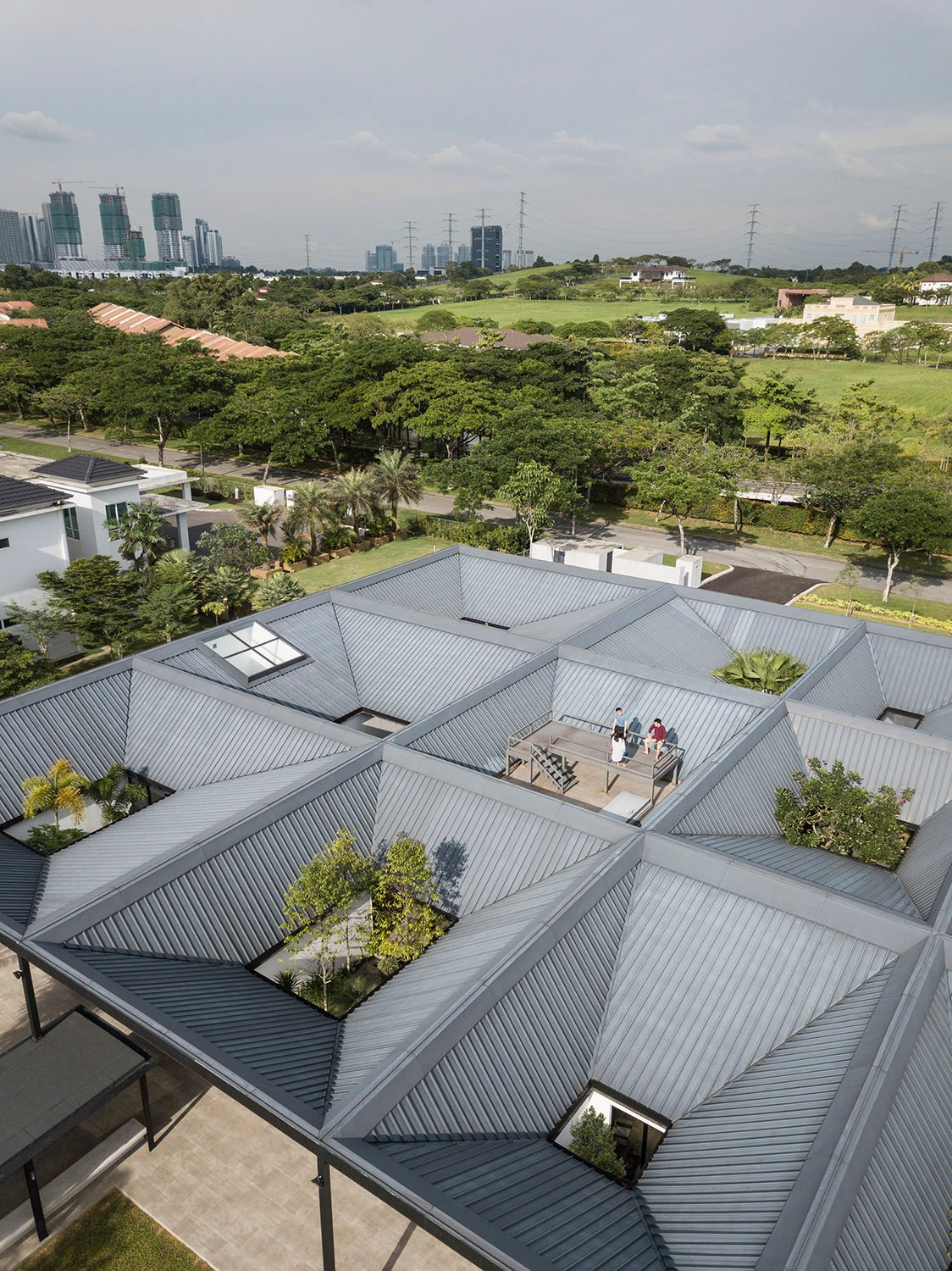 Aerial view of the house showcasing its characteristic inverted timber roofs, forming a grid of courtyards. Fabian Ong