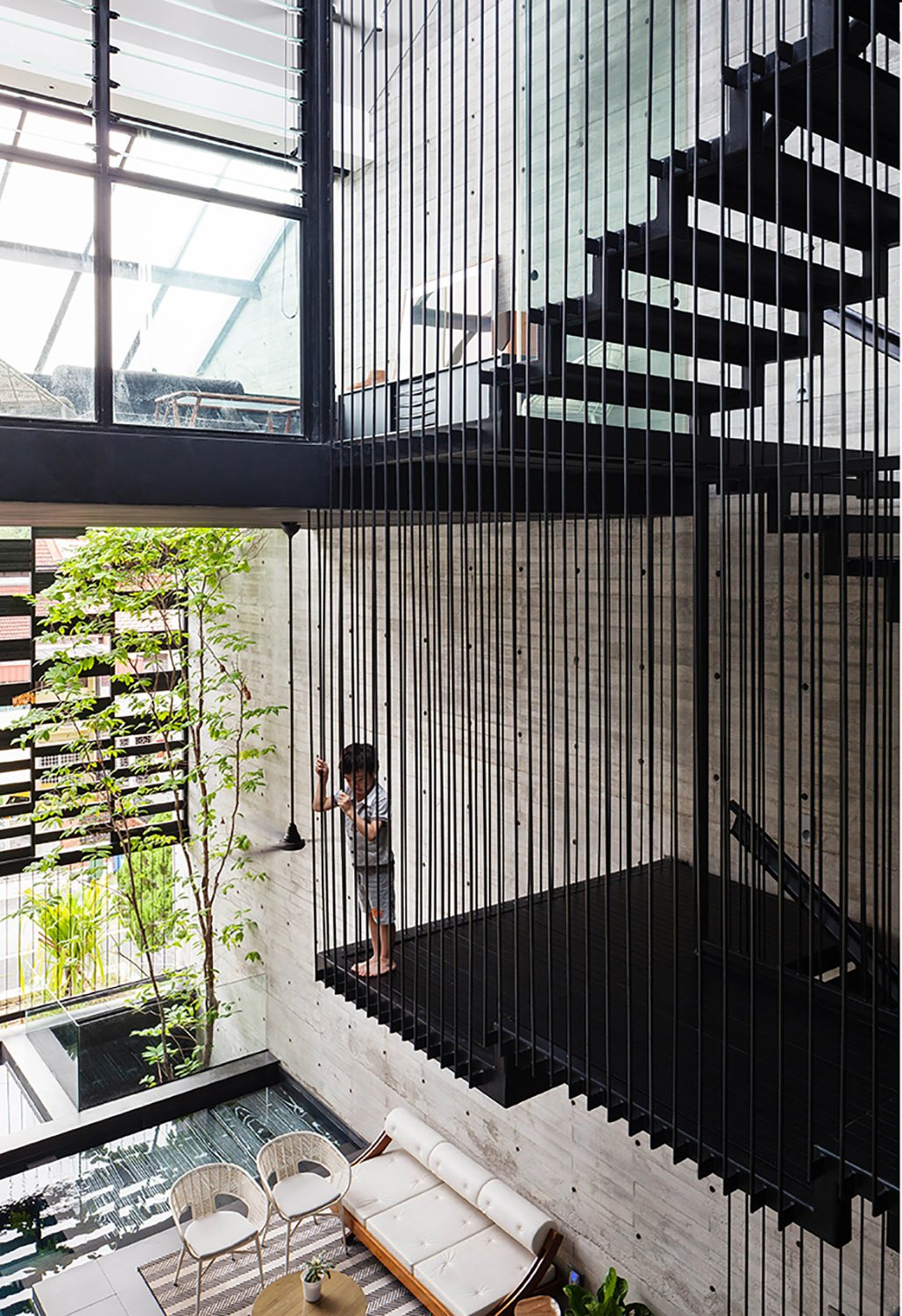 A suspended steel rod staircase forms a key feature in the double volume central atrium. Fabian Ong