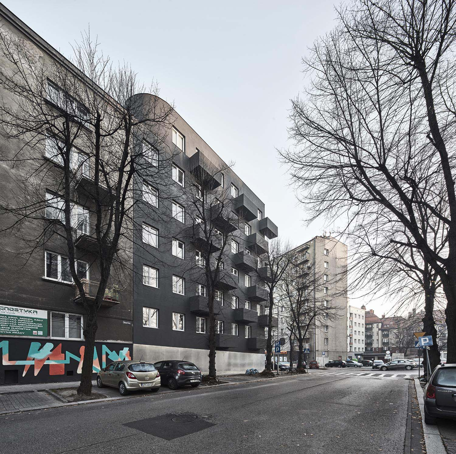 View from the south - west. Dark facade and the characteristic motif of the connection between windows and balconies was taken from the neighboring building Aleksander Rutkowski