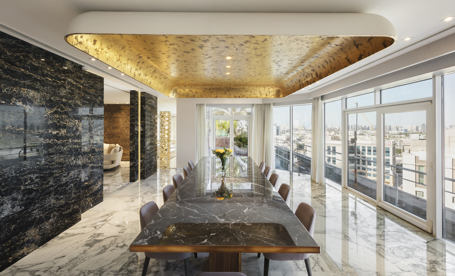 The sculptural ceiling above the dining table is embellished with gold leaf that adorns the architectural element as if it were a precious piece of art. Duccio Grassi conceived the partitions as individual Mohamed Somji