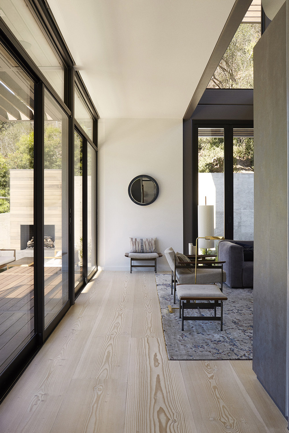 The muted, almost Nordic palette directs the focus outward. Seen through the ground floor's expansive glass wall. Miller Mobley