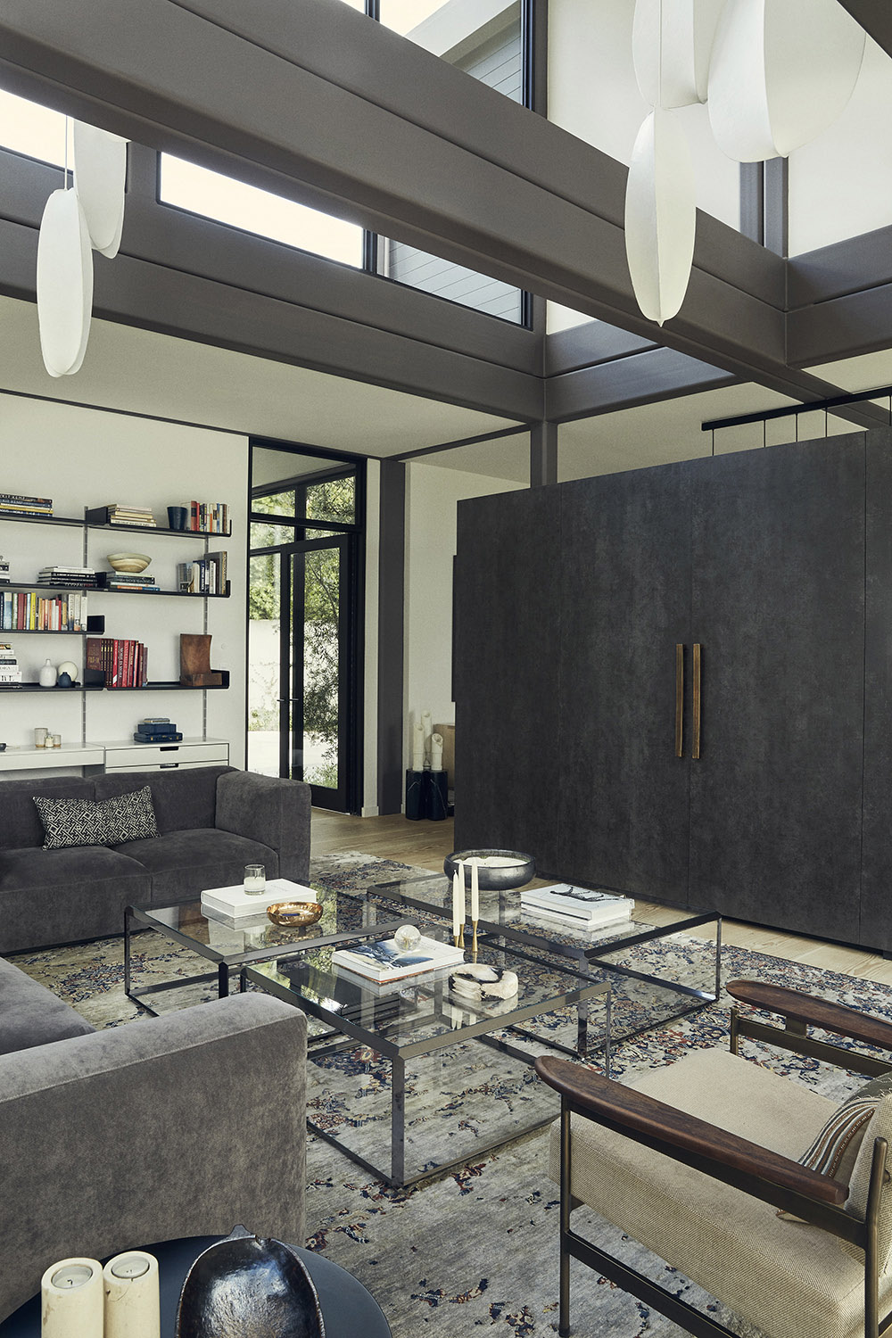 In the living area, Mori pendants by Rich Brilliant Willing hang above an Erased Heritage rug by Jan Kath. Miller Mobley