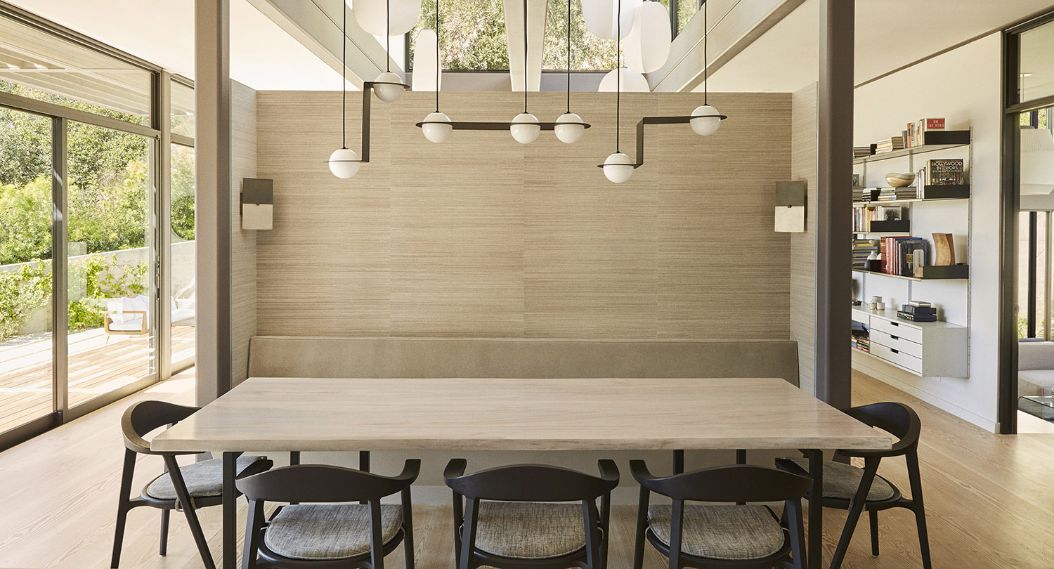 A banquette upholstered in Holly Hunt fabric surround a live-edge maple table by Camilla House. Miller Mobley