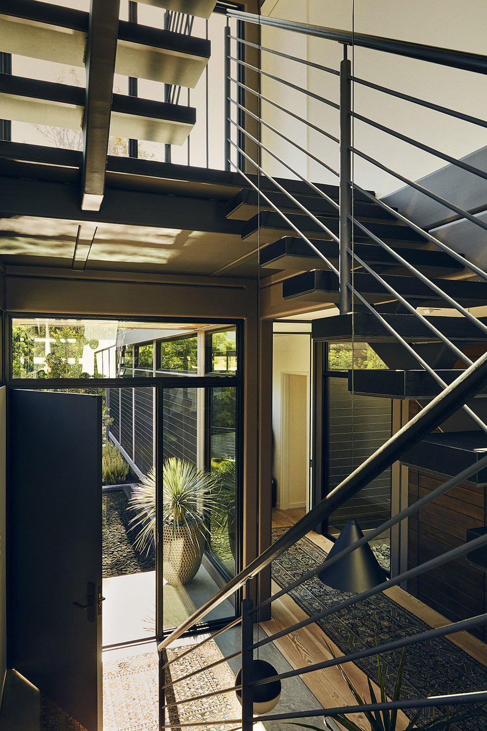 Near the front door, charred oak treads float on a blackened steel stringer to the master suite and on to the roof. Miller Mobley