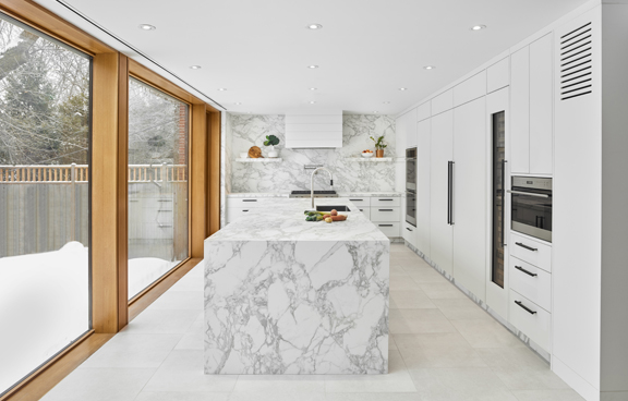 View of the kitchen with floor to ceiling windows to left, laminam kitchen and backsplash and all white cabinetry Scott Norsworthy