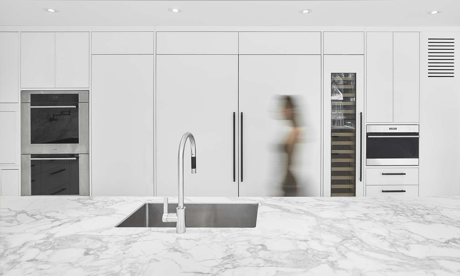View of all white kitchen millwork as the backdrop for the view outside Scott Norsworthy