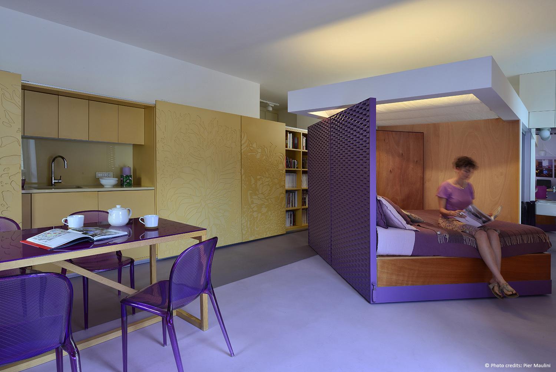 La sera il cubo gira e svela la stanza da notte, i pannelli scorrevoli aprono l'intera parete che contiene la cucina, gli elettrodomestici e la dispensa. Pier Maulini
