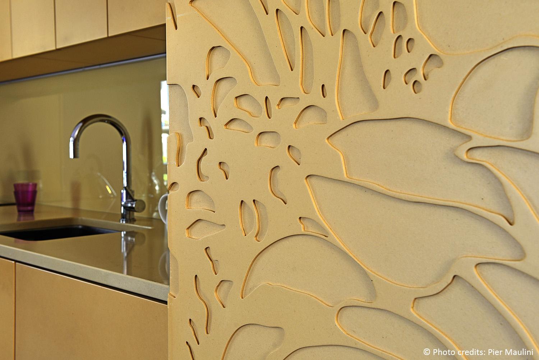 Dettaglio dell cucina: MDF alleggerito, finitura naturale, inciso seguendo un disegno vettoriale, grazie ad una macchina a taglio laser, retro in vetro colorato e temperato, top cucina in quarzo. Pier Maulini