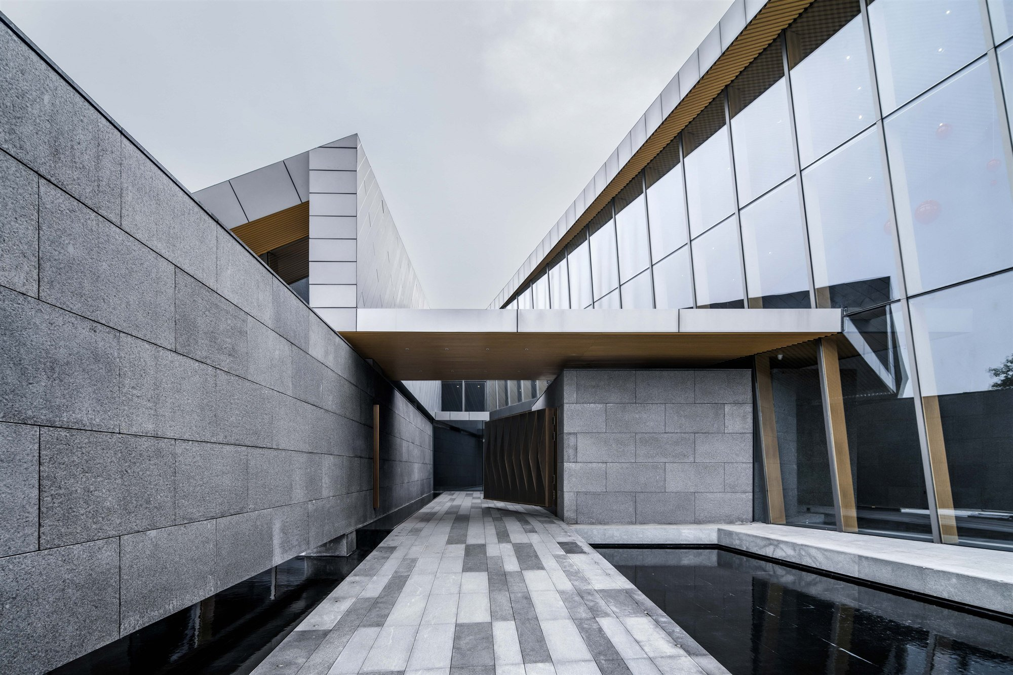 View street view and entrance gate from inner courtyard. Lacime Architects