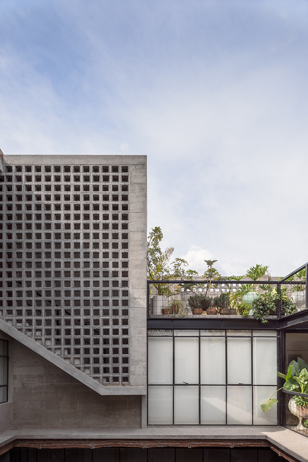 A perforated concrete prism, protrudes from the patio's façade Luis Gallardo / LGM Studio
