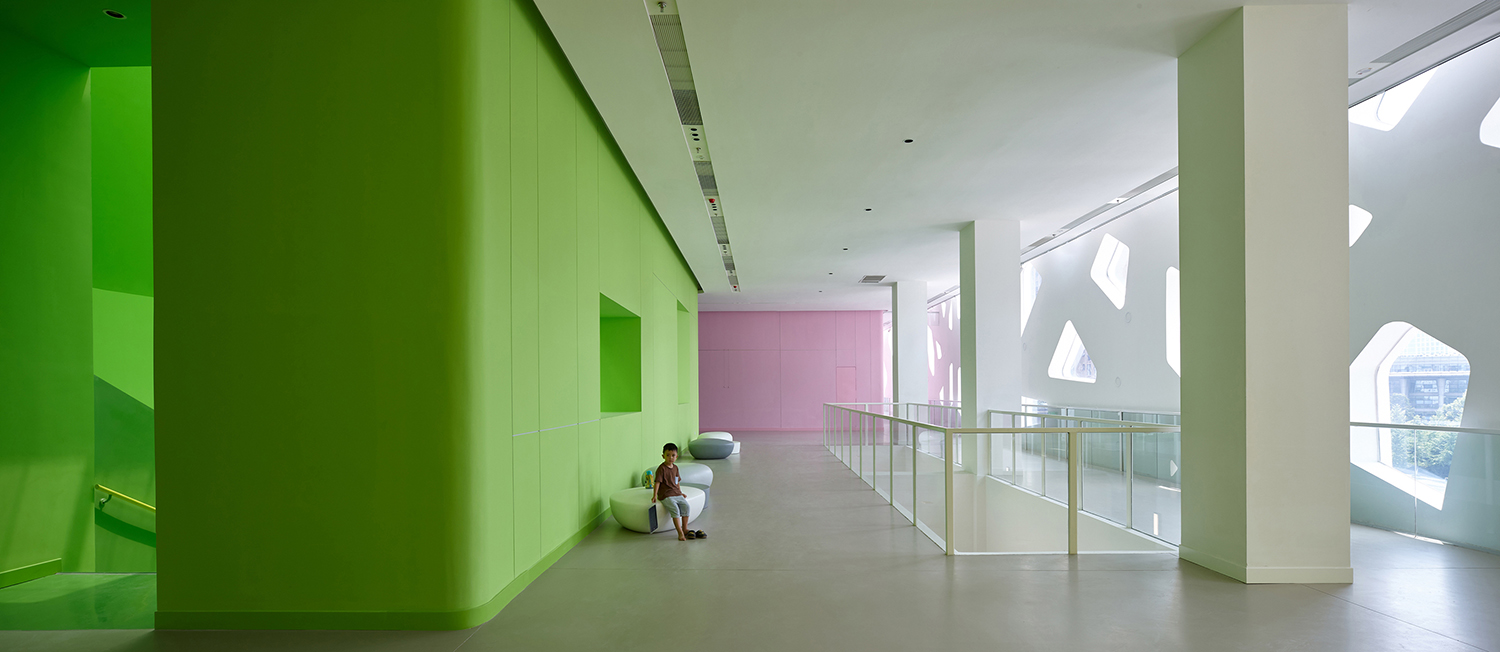 Open space on 3rd floor with the green staircase to the left, the perforated building skin to the right and the small exhibition hall in pink beyond Su Chen