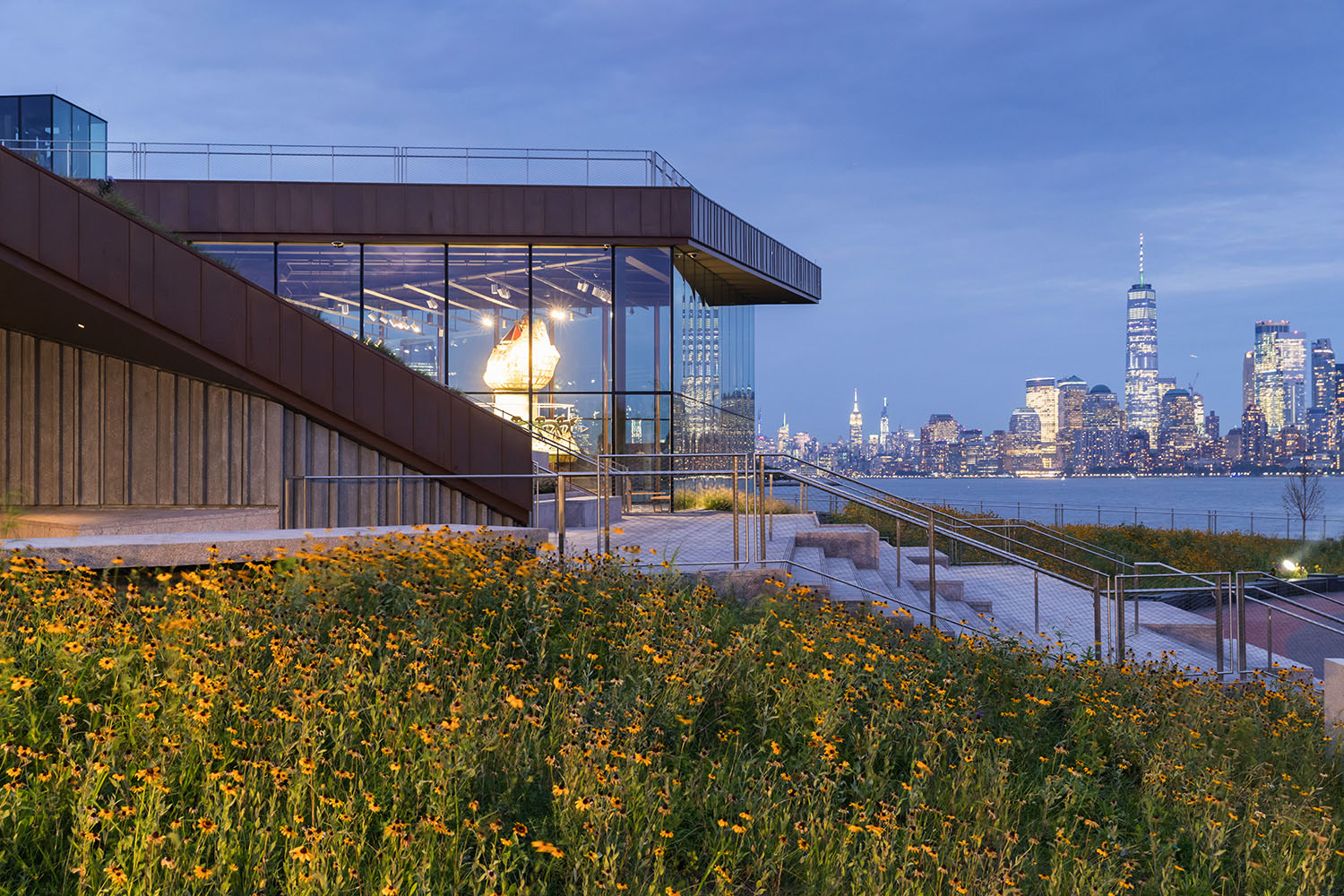 Viewed at dusk: artful composition of the museum, the torch, meadow of native flowers, and Manhattan skyline beyond. Copyright Iwan Baan