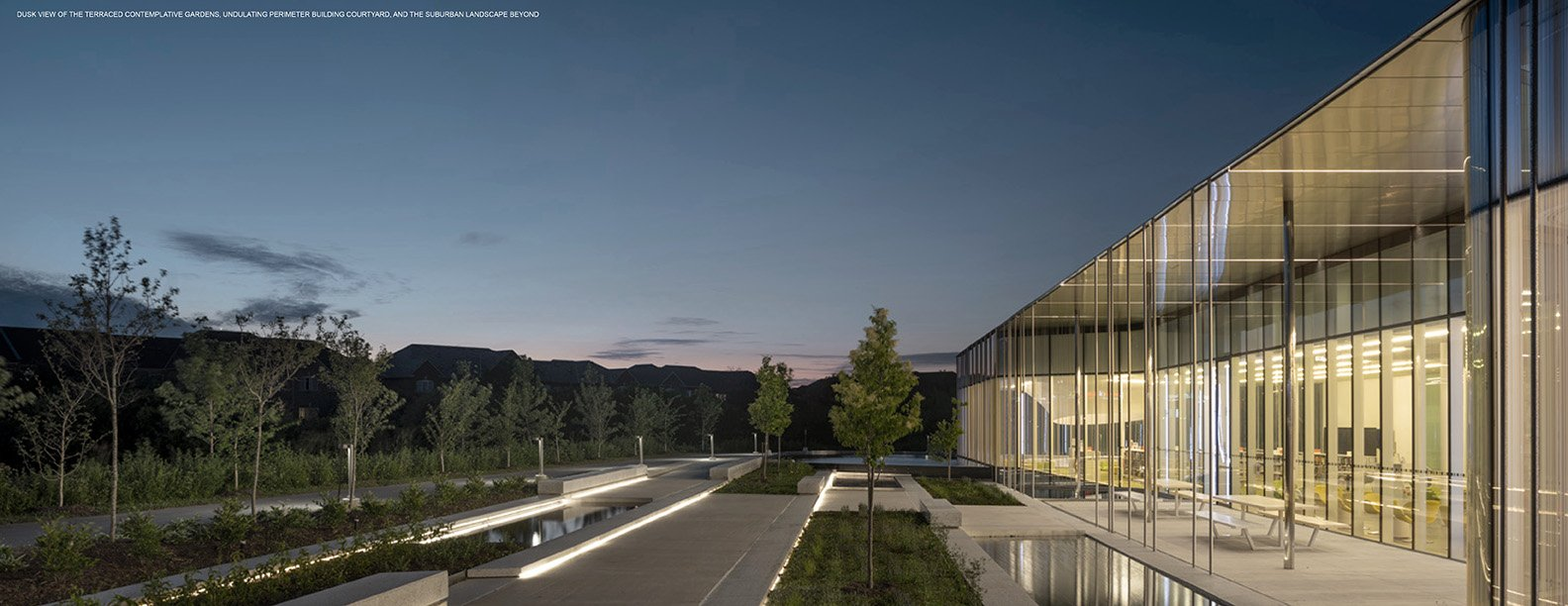 DUSK VIEW OF THE TERRACED CONTEMPLATIVE GARDENS, UNDULATING PERIMETER BUILDING COURTYARD, AND THE SUBURBAN LANDSCAPE BEYOND Nic Lehoux