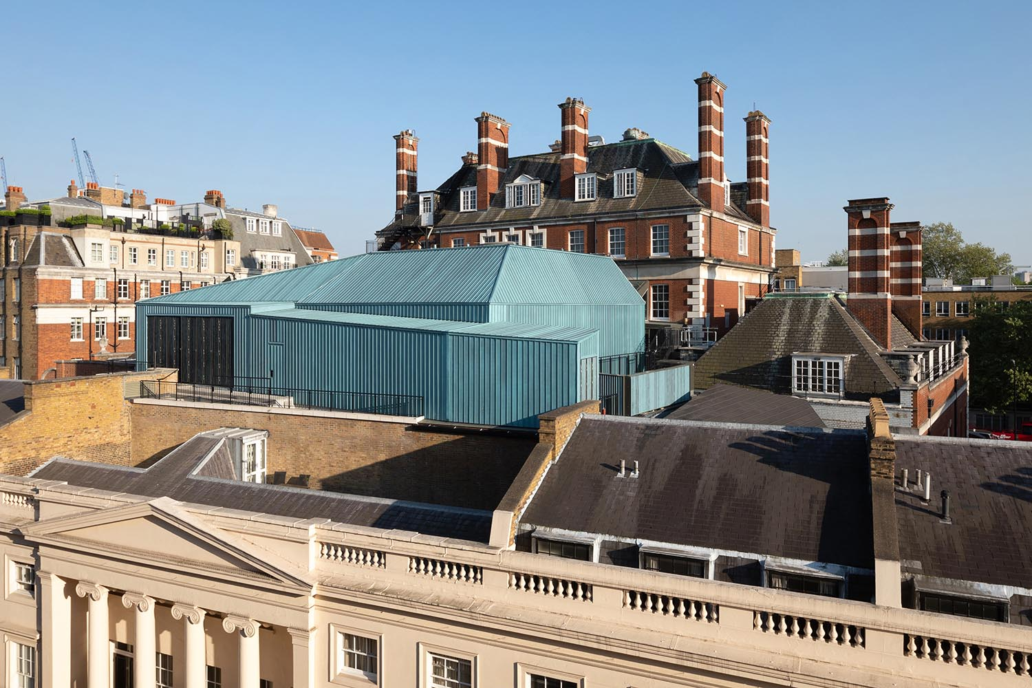 The new Recital Hall within its listed building setting, clad in blue pre-patinated copper and entirely imperceptible from street level Adam Scott