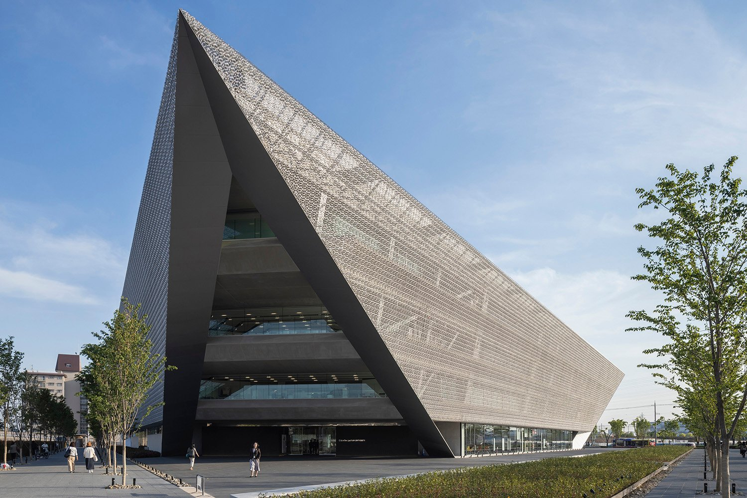 Daytime View. Inverted triangular pyramid covered with stainless-steel eco-screen is open public Shinkenchiku-sha