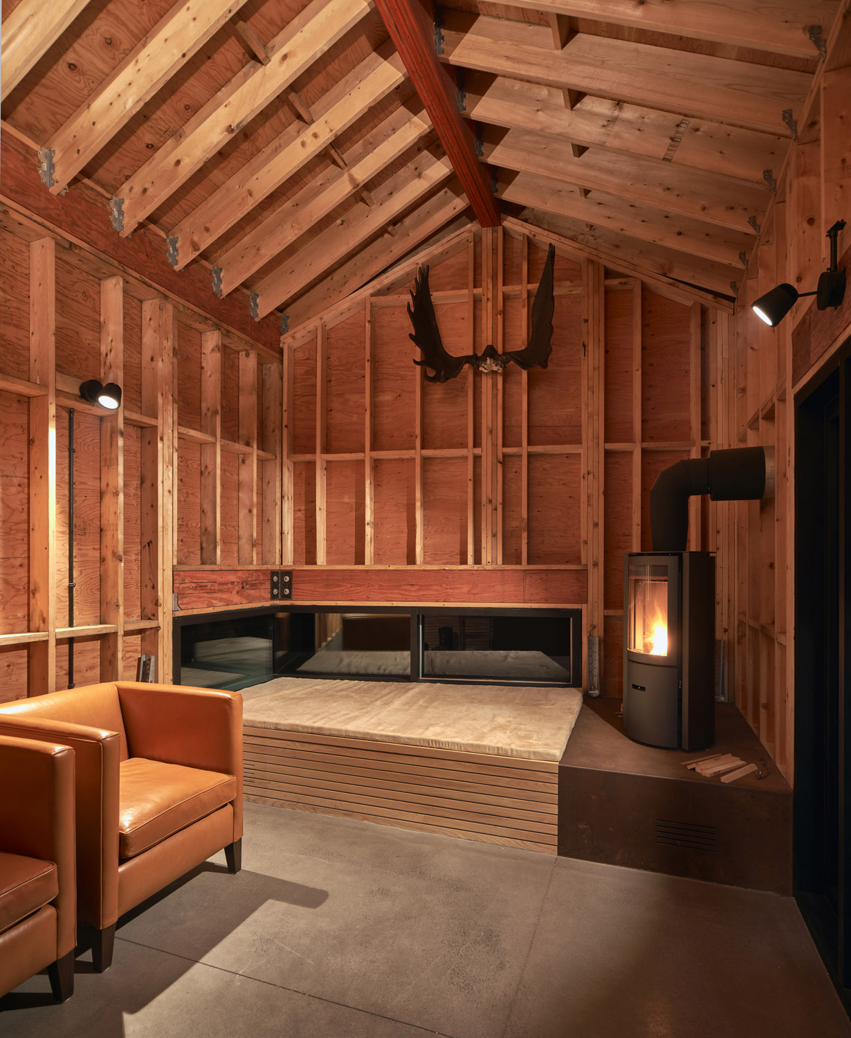 The rustic shed with plinth/hearth functions as a retreat for the client's children Doublespace Photography Inc