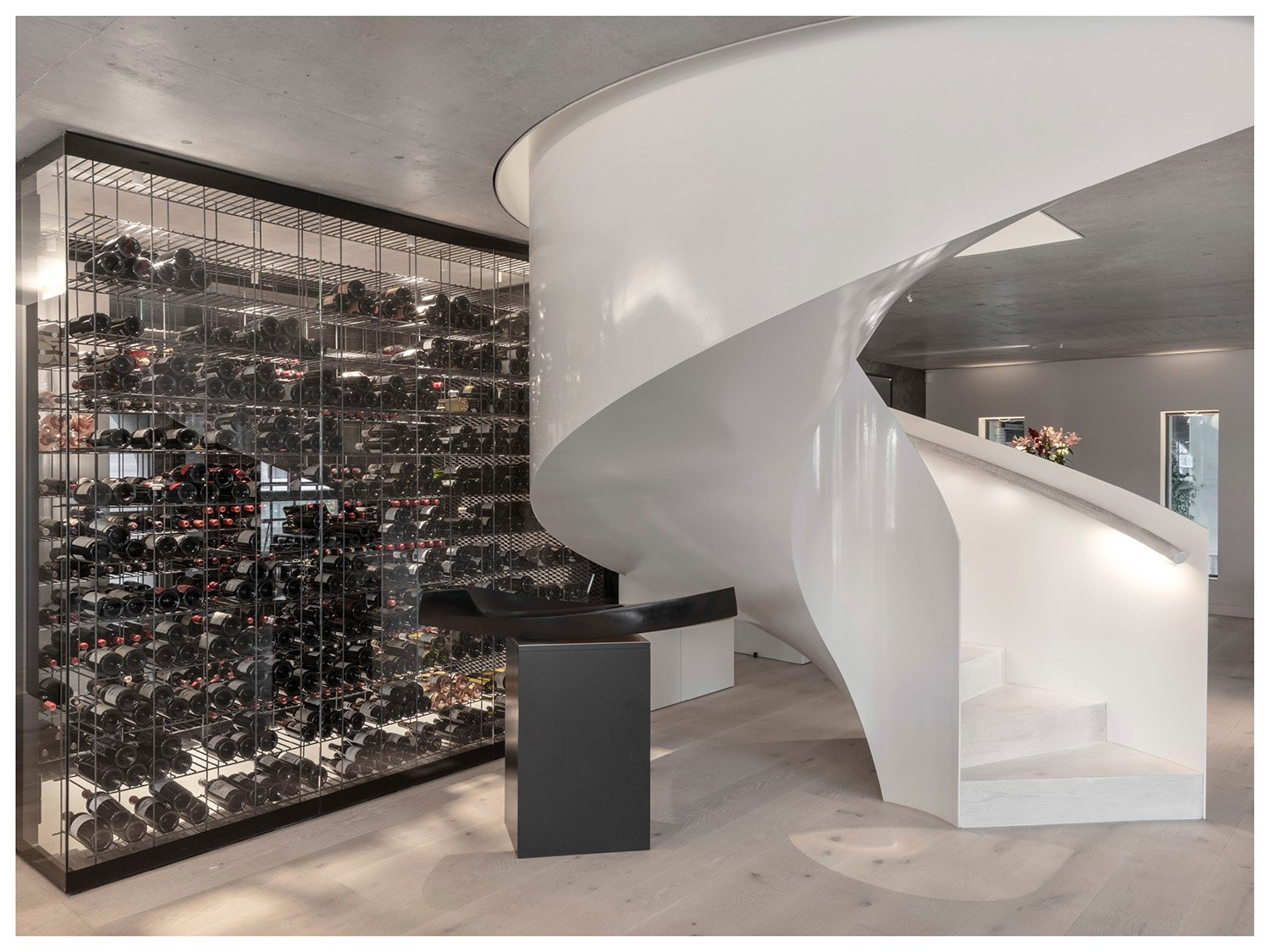 The white, monolithic-like spiral staircase vertically connects the three floors. Delphine Burtin}