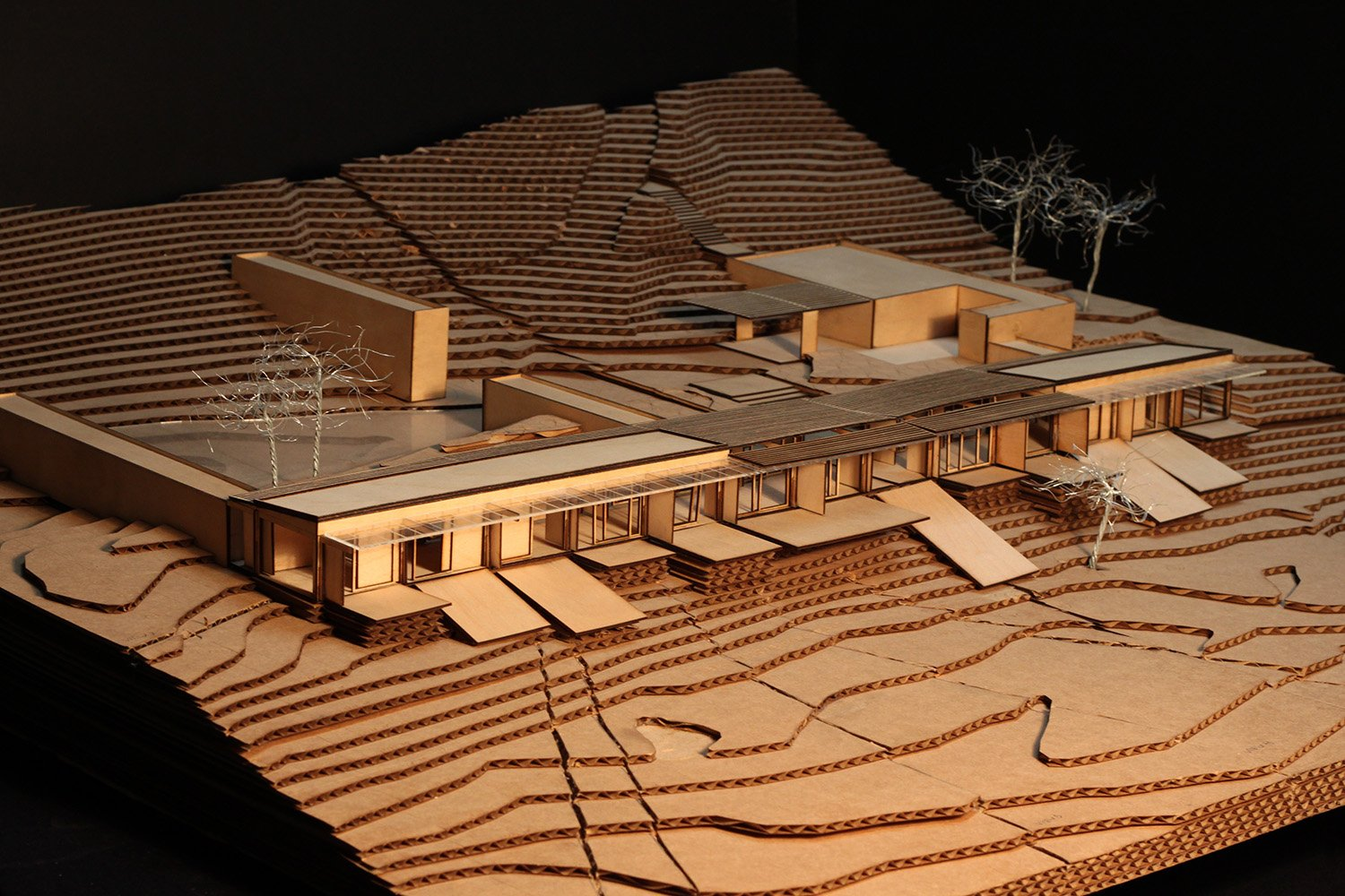 Early design process model in laser cut wood and cardboard to study integration of structure into the sloping site. View from southeast. Anderson Anderson Architecture}