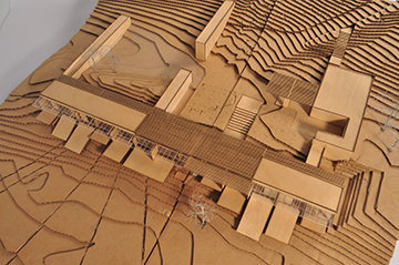Early design process model in laser cut wood and cardboard to study integration of structure into the sloping site. View from southwest. Anderson Anderson Architecture}