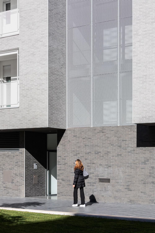 Dettaglio della corte interna: mattoncini grigi e lamiera metallica Marco Cappelletti