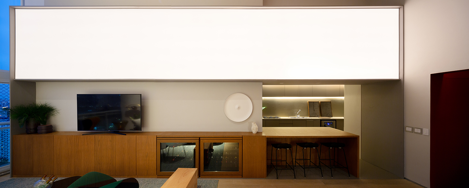 The furniture that separates the kitchen from the living room received tensoflex as a lighting device that simulates the sunrise and sunset light Pedro Kok