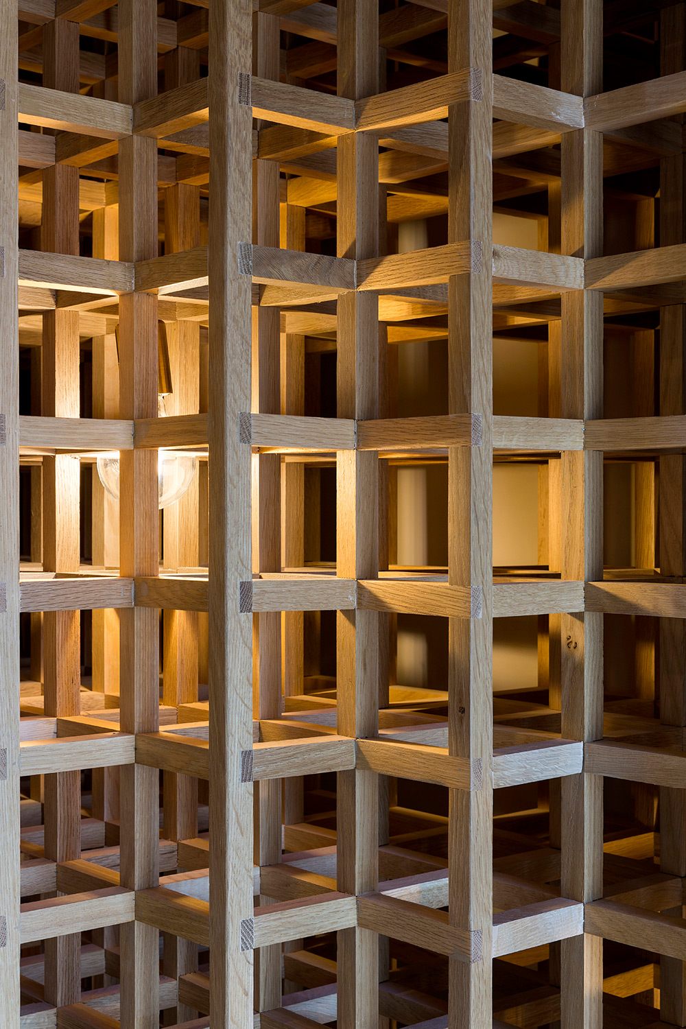 The entire space is enveloped in tens of thousands of hollow, white oak cubes assembled, with accent lighting that gives the restaurant a celestial feel. Filippo Bamberghi