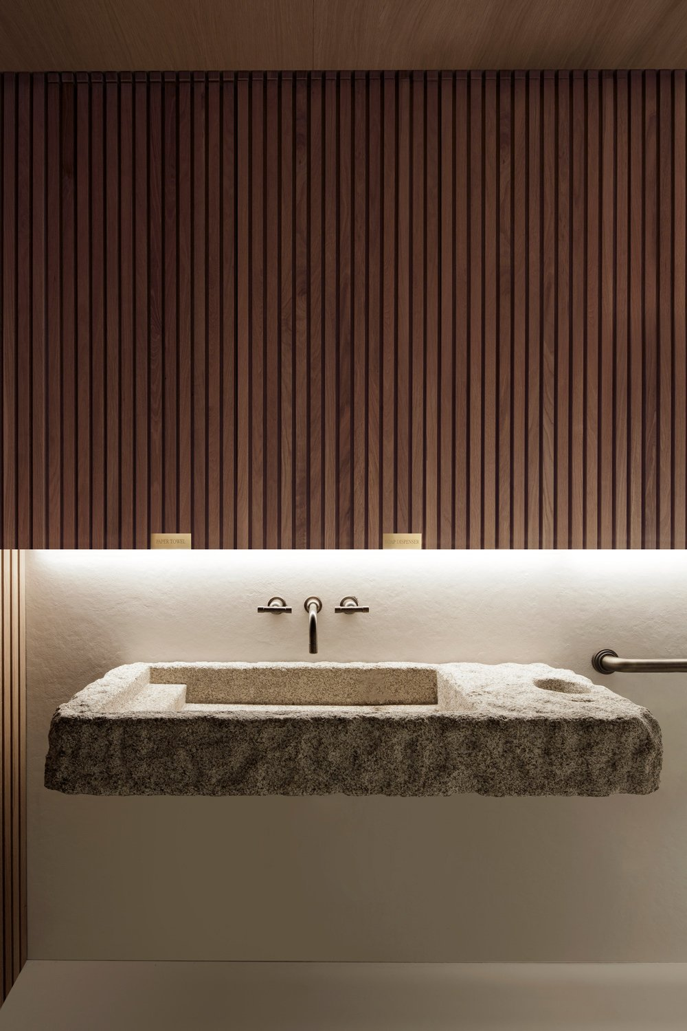 The Restroom, with stone mounted sink and wood slot panel. Filippo Bamberghi