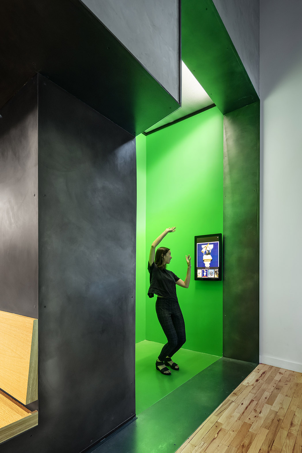 A green-screen photo alcove -- directly visible through the storefront facade -- lets visitors insert their own image into historic posters. Photography, Michael Moran / OTTO