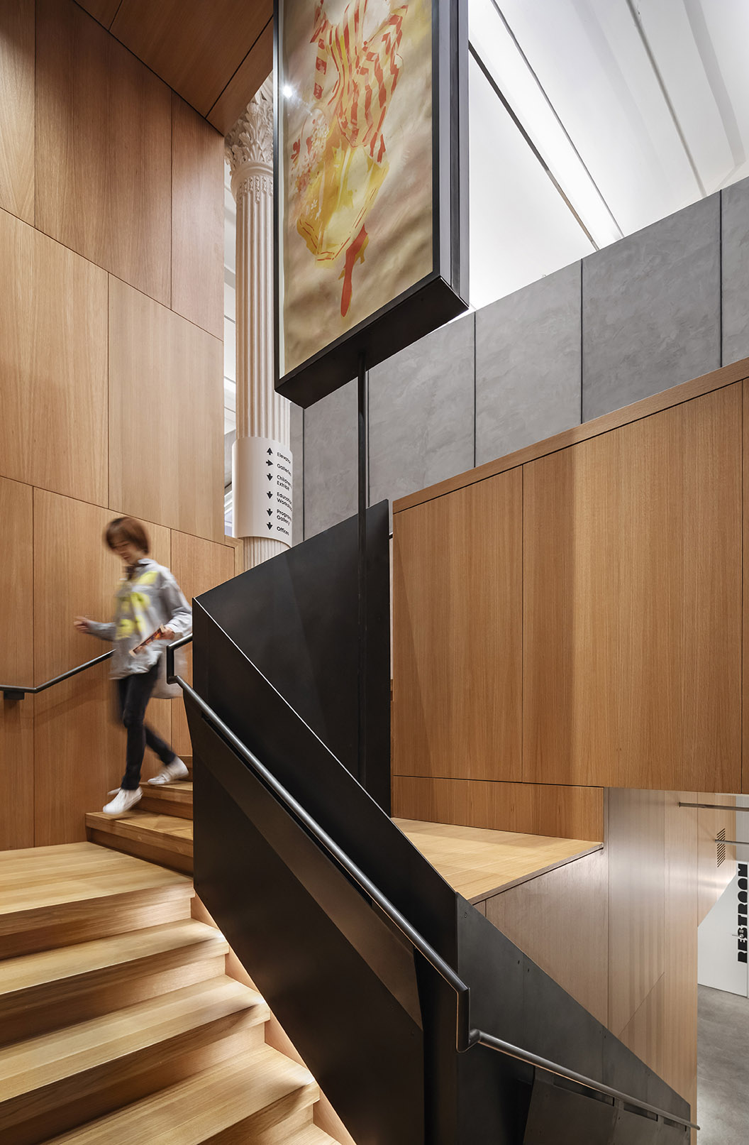 Descending to the basement, a staircase combines rift-sawn white oak with chemically blackened steel. Photography, Michael Moran / OTTO