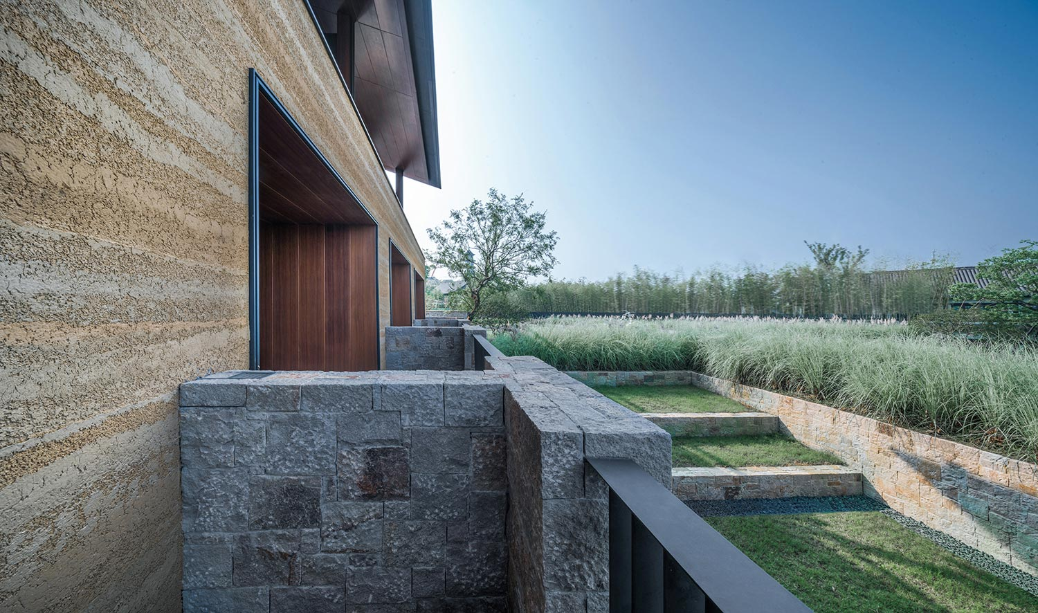 Landscape fits with rammed earth building Lei Sun