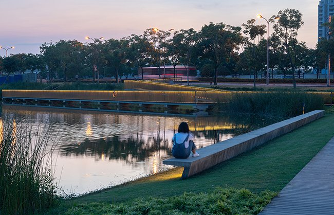 Integrated with LED light fixtures, furniture inspired by the shape of aircraft wings and lit handrails allow for evening use along the canal. Insaw Photography