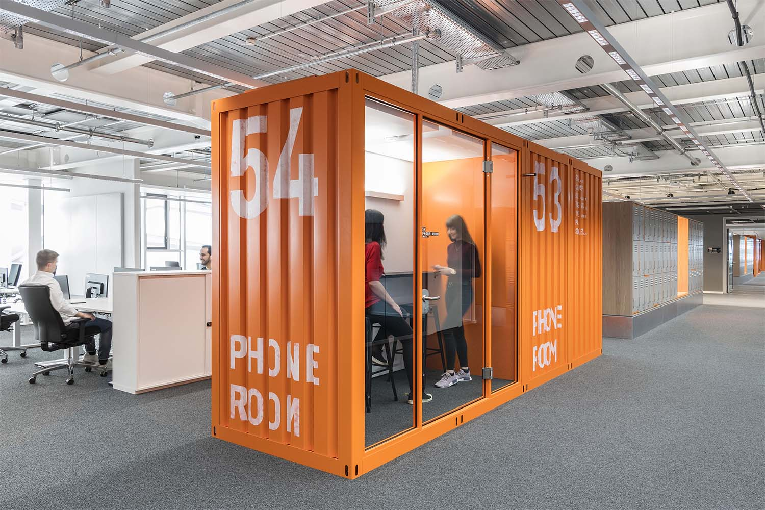 A modular system of customized work booths resembling shipping containers structures the workspace and provides a broad array of functions. David Matthiessen