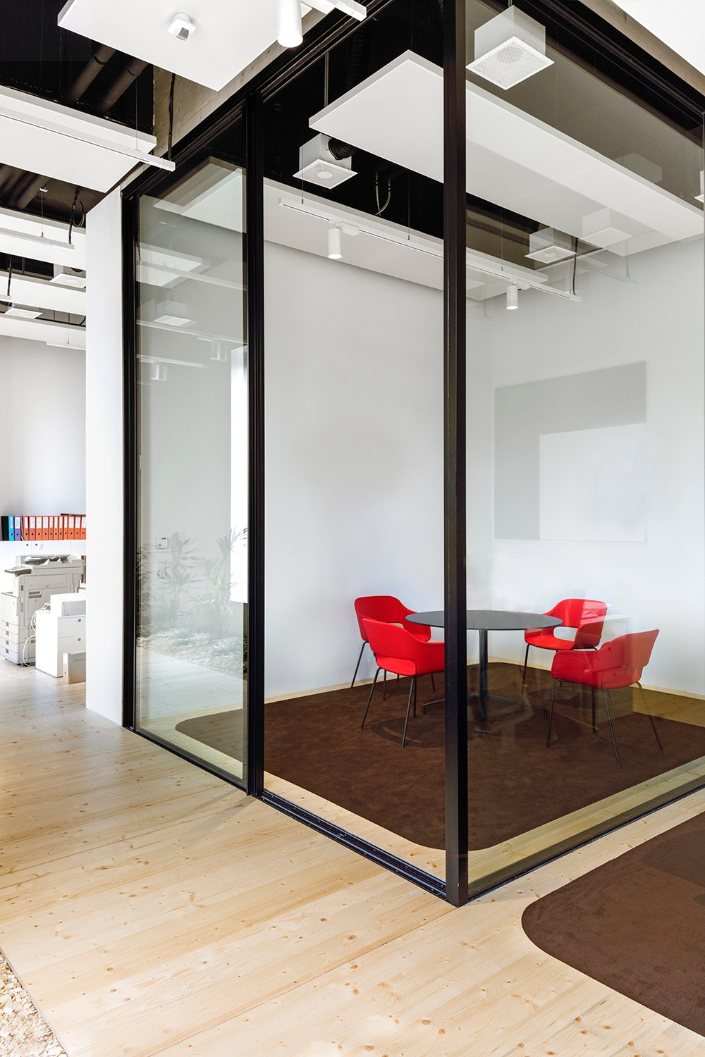 Private offices delineate open shared workspaces and are enclosed by sliding glass partitions. Delphine Burtin
