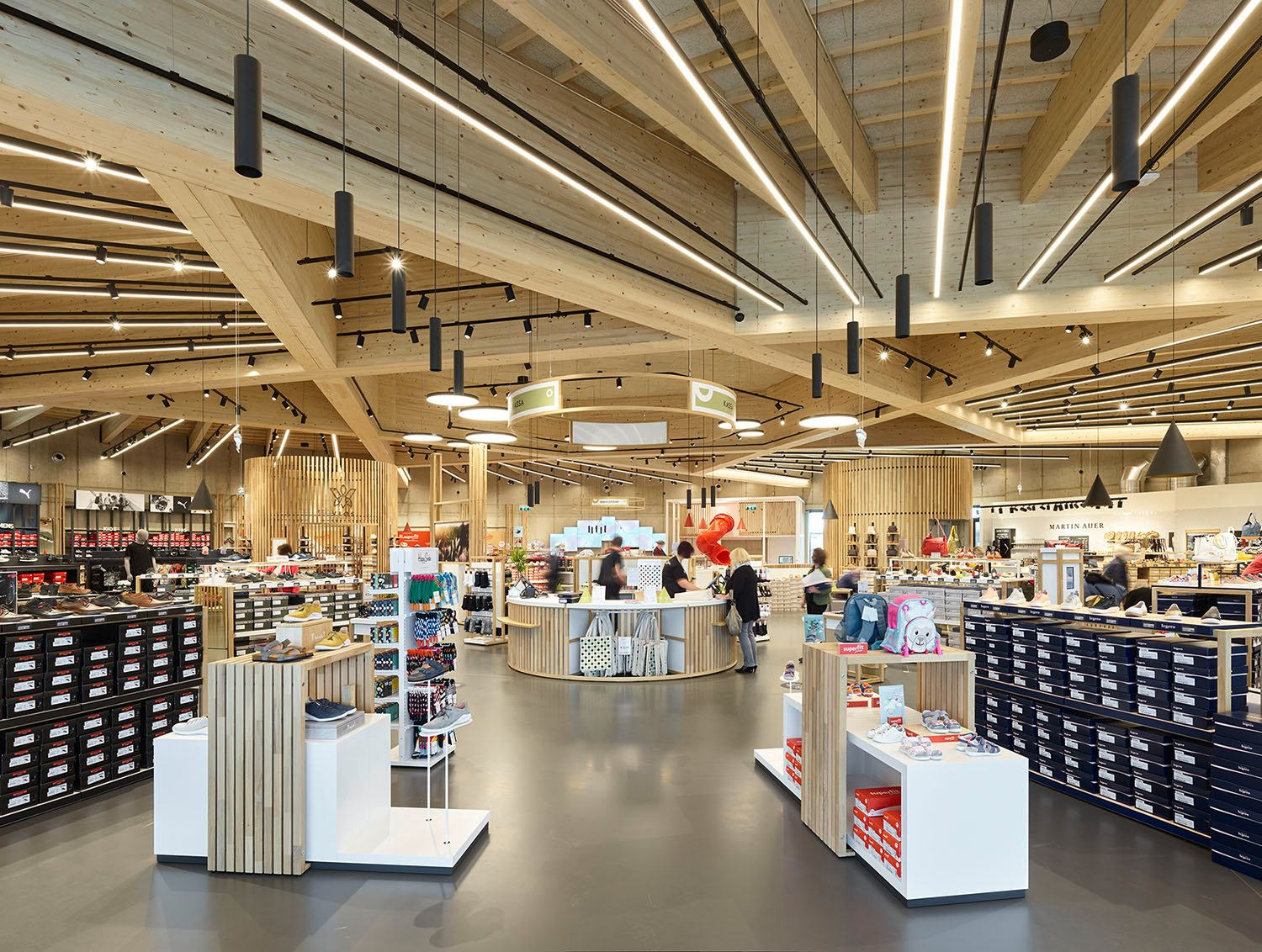 The column-free space of the shoe outlet is spanned by a star-shaped wooden supporting structure. Bruno Klomfar