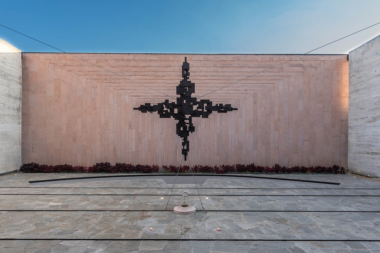To the bottom, the courtyard holds a suspended steel cross, designed and manufactured in-house Jaime Navarro Soto