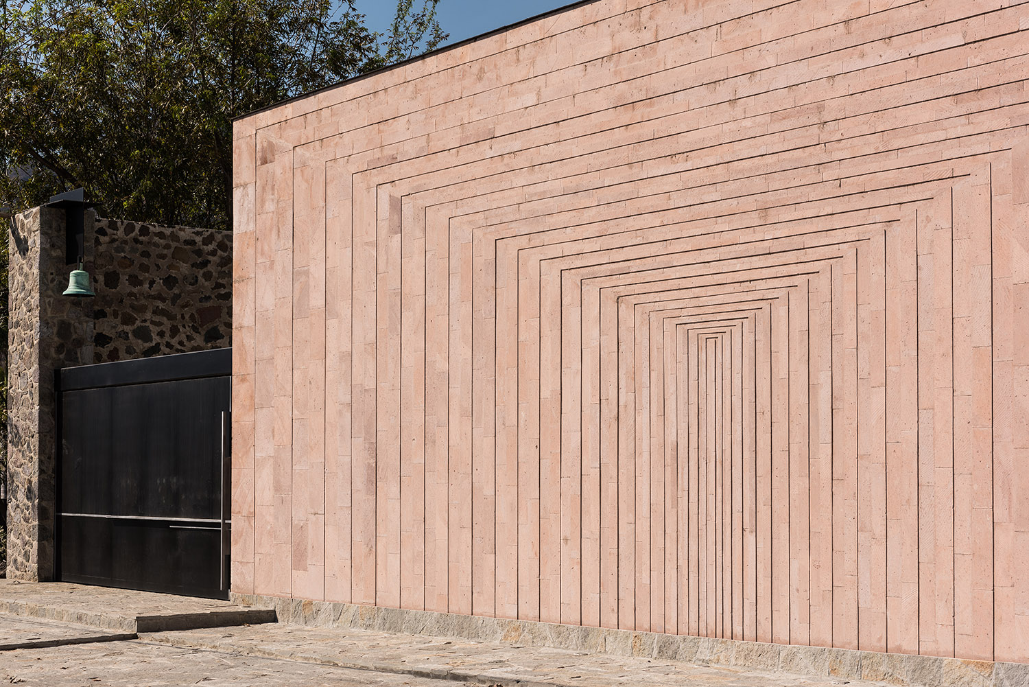 A pink stone wall was designed with a geometrical path that emphasize the patio's depth. Jaime Navarro Soto