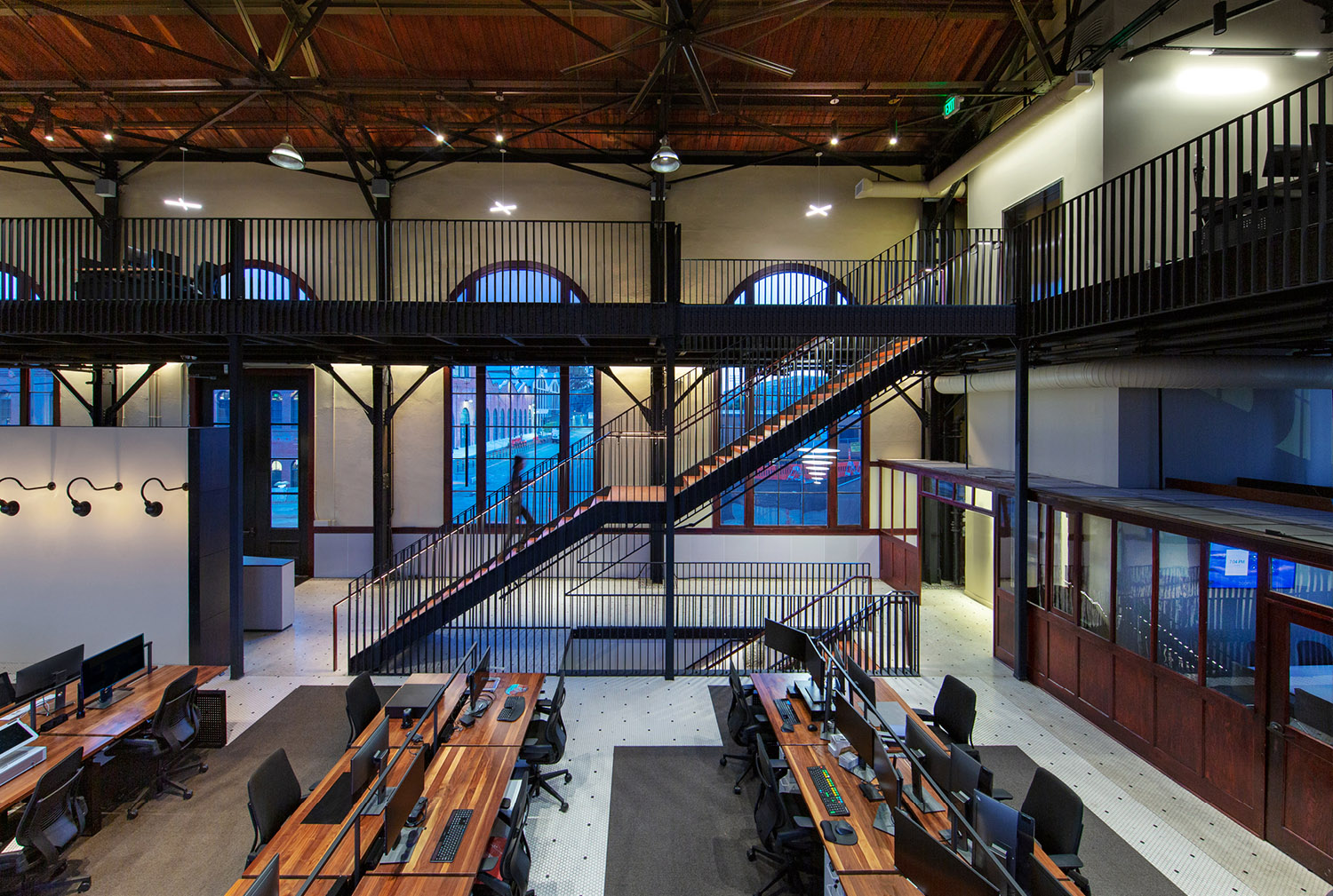 The heavy-timber construction of the new mezzanine and new stair treads is detailed to complement the exposed historic wood roof structure above, while the new steel balustrades at mezzanine guard rails and stair recall the historic exposed steel roof tru Billy Hustace