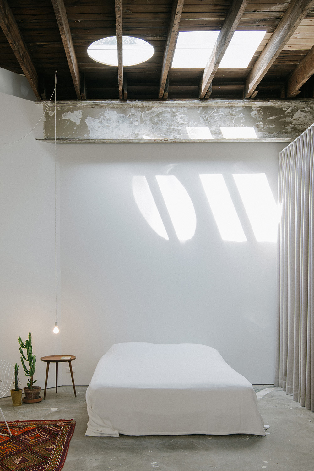 Photograph showing main bedroom space with new toplights. The original structure - the joists - were not cut for the skylight installation. Florian Holzherr