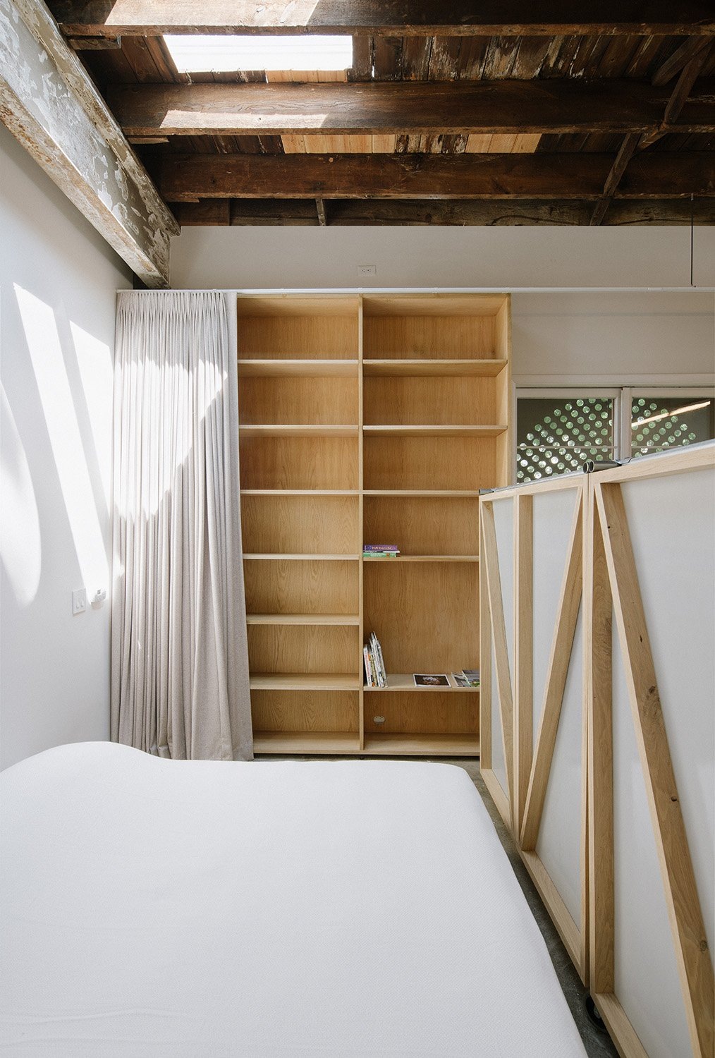Photograph showing the bedroom partitioned off using two wardrobes on casters. All furniture for the project was designed to be able to accommodate the occupants' basic needs, and also be able to move to o Florian Holzherr