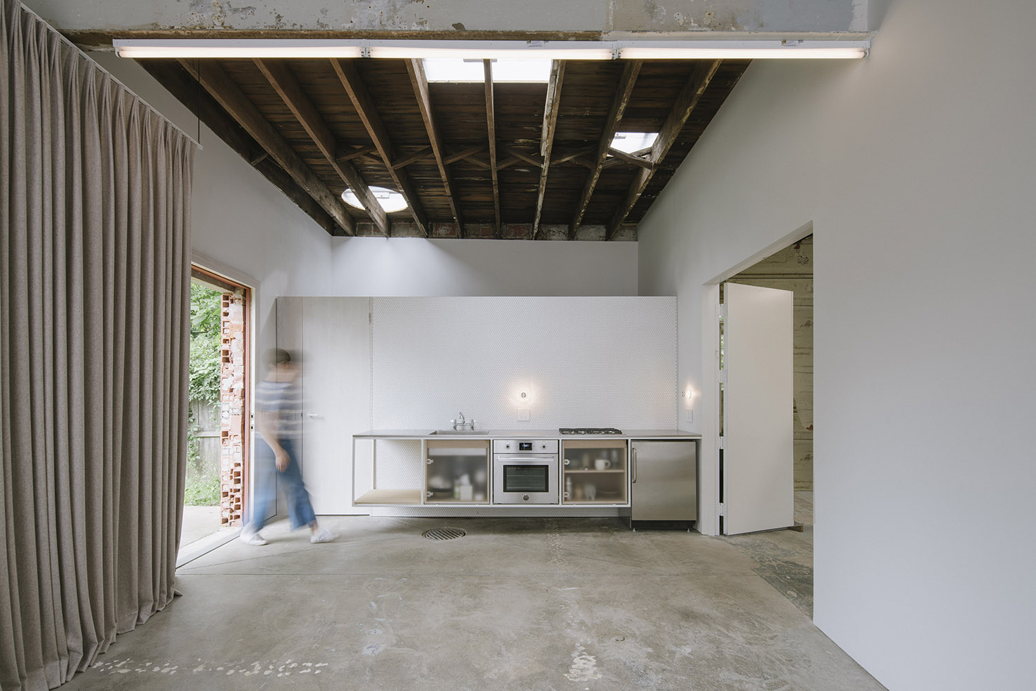 Photograph showing the infrastructure zone for the small space - a wall-hung kitchen area sits directly in front of a bathroom and laundry area. The utilities are condensed into the smallest area possible Florian Holzherr