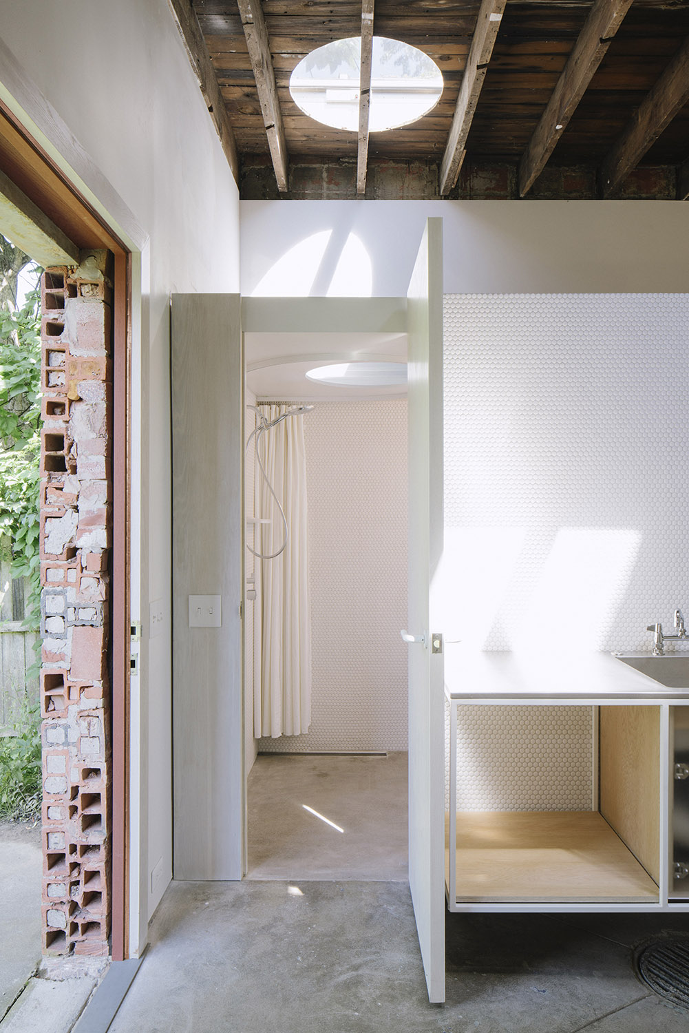 Photograph showing the entry to the bathroom, bathed in natural light from a skylight directly aligned over the shower area. The tiny square footage of the spaces is compensated for by the generous vertica Florian Holzherr