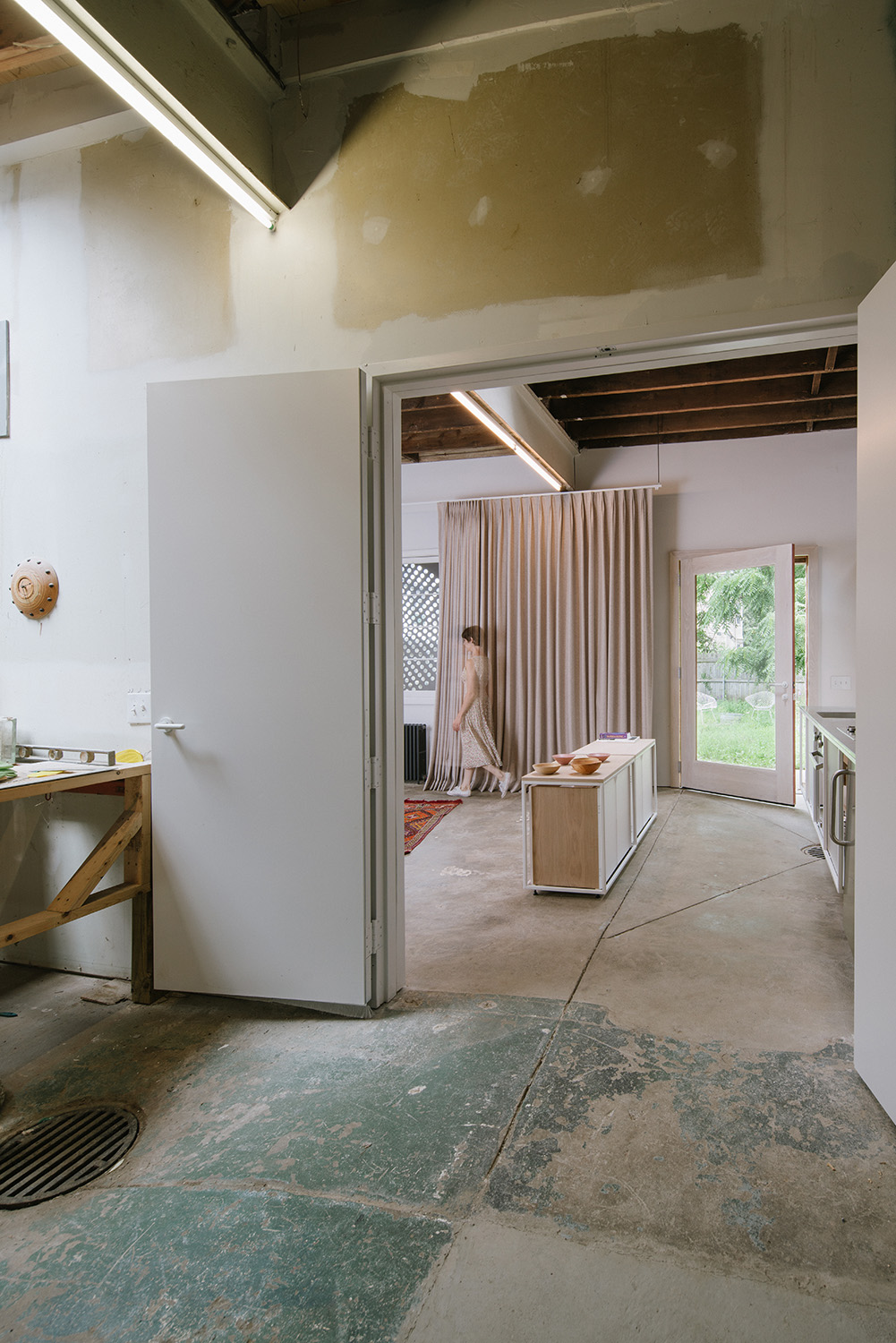 Photograph showing a view from the rough, un-climatized workshop, into the apartment space. Through-views (from the workshop, through the apartment, into the garden) are deliberate and intended to counter- Florian Holzherr