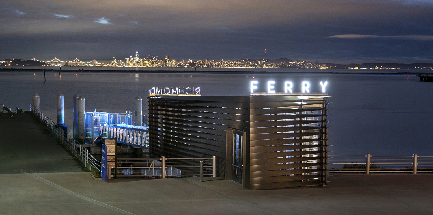 The ferry terminal acts as a symbol for the city of Richmond along its coastline. The Bay Bridge and San Francisco are visible across the bay. Billy Hustace