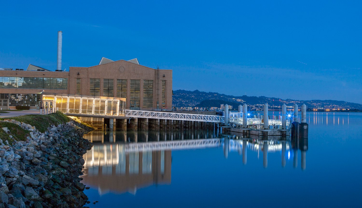 The terminal's western facade reflects on the surface of the Bay. Beyond to the east is the historic Ford Assembly Building, Marina Bay, and the Berkeley hills. Billy Hustace